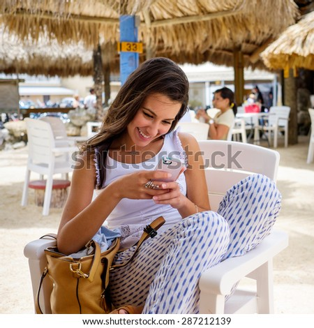Beautiful young woman enjoying the outdoors in a tiki style restaurant setting in the Florida Keys.