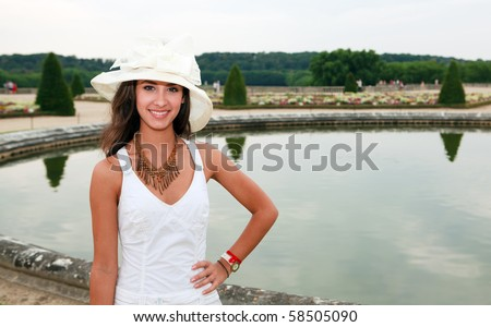Beautiful young woman enjoying the Palace of Versailles Gardens in Paris, France.