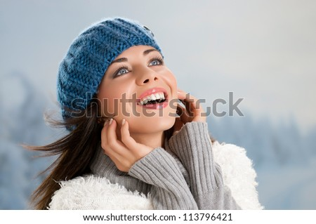 Beautiful young woman enjoying the sun in a cold winter day