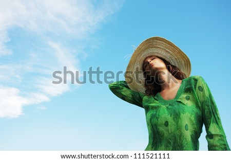 Beautiful young woman enjoying the sunny day against blue sky