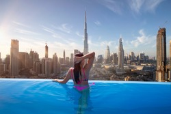 Beautiful young woman enjoys the panoramic view from an infinity pool on downtown Dubai