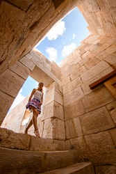 beautiful young woman enters building ruins of amphitheatre and assembly hall ancient Lycian city Patara.