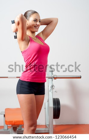 Beautiful young woman exercising with dumbbells in the gym.