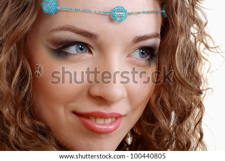 beautiful young woman face close up with hippie art make up and false eyelashes