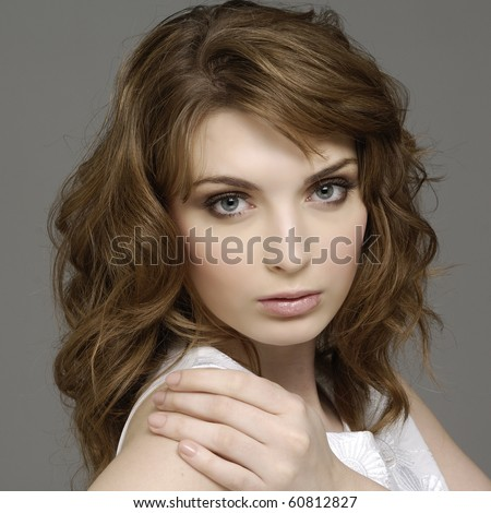 Beautiful young woman face. Isolated over gray