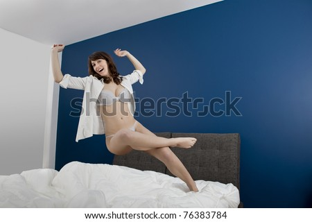 Beautiful young woman falling to the bed