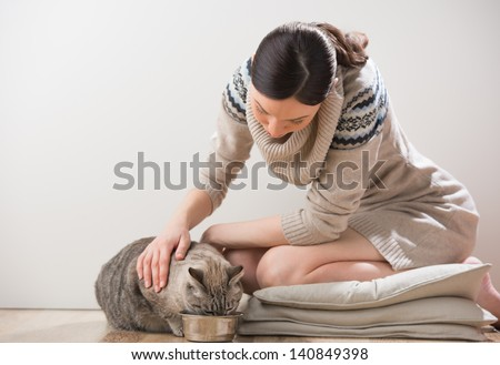 Beautiful young woman feeding her cat at home