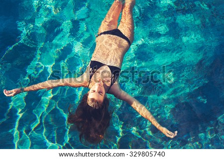Stock Photo Beautiful young woman floating in pool relaxing