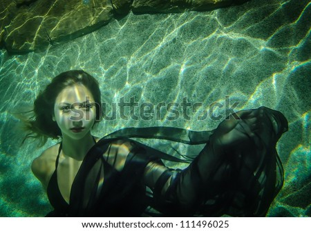 Beautiful young woman floating underwater in a black dress