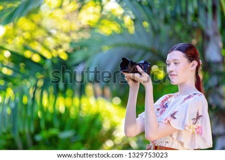 Beautiful young woman focusing her digital camera to take a photo in a colorful garden