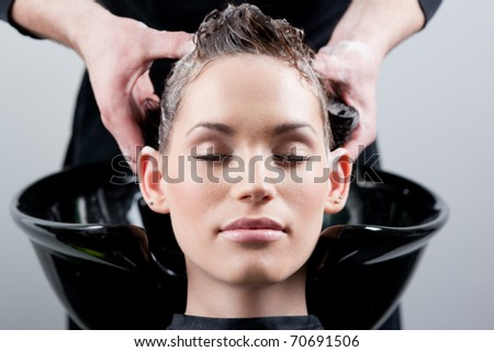 Beautiful young woman getting a hair wash. In a hair salon. Close up.