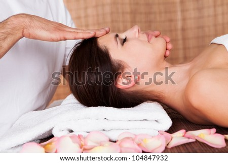 Beautiful young woman getting face massage at spa