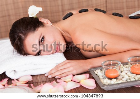 Beautiful young woman getting hot stone therapy at spa salon