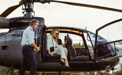 Beautiful young woman getting out of a helicopter with male pilot standing by. Woman travelling by her helicopter.