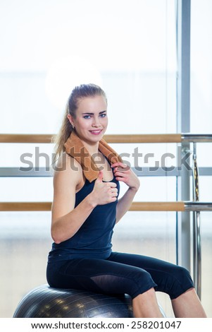 Beautiful young woman girl after physical excercise in fitness center gym  sitting on gymnastics ball. #258201047