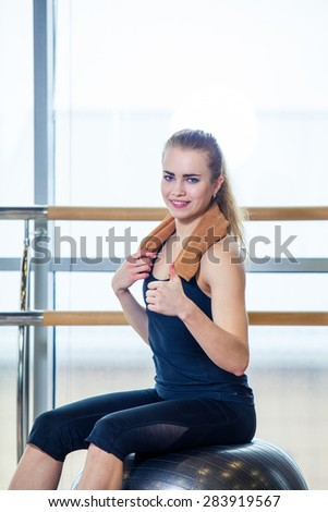 Beautiful young woman girl after physical excercise in fitness center gym  sitting on gymnastics ball #283919567
