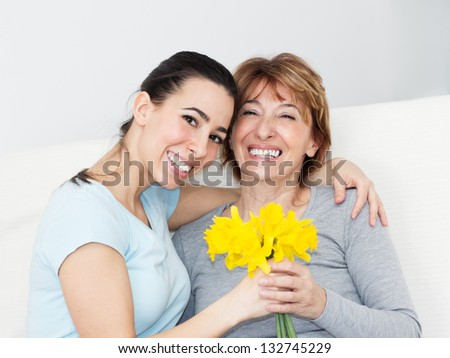 Beautiful young woman giving to her mother flowers for Mother's Day.