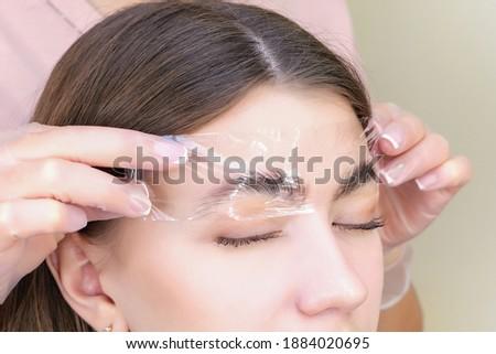 Beautiful young woman got correction of eyebrows in a beauty salon. eyebrow lamination Zdjęcia stock ©