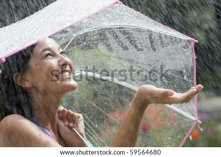 Beautiful young woman grins as she holds out her palm to catch falling water. She is holding an umbrella over her head. Horizontal shot.