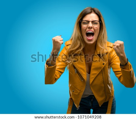 Beautiful young woman happy and excited celebrating victory expressing big success, power, energy and positive emotions. Celebrates new job joyful, blue background #1071049208