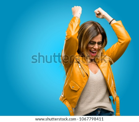 Beautiful young woman happy and excited expressing winning gesture. Successful and celebrating victory, triumphant, blue background #1067798411