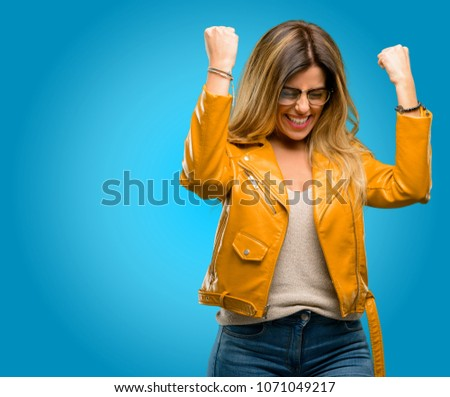 Beautiful young woman happy and excited expressing winning gesture. Successful and celebrating victory, triumphant, blue background #1071049217