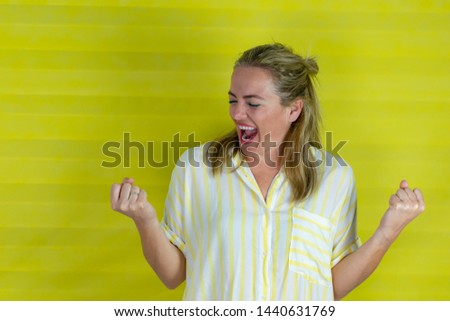 beautiful young woman happy and excited expressing winning gesture . Successful and celebrating victory, triumphant, yellow background - Image #1440631769