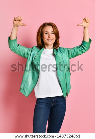 Beautiful young woman happy and excited expressing winning gesture. Successful and celebrating victory, triumphant, pink background #1487324861