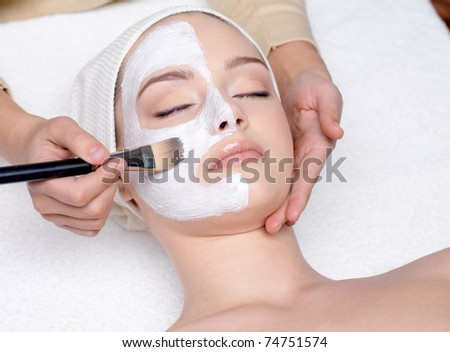 Beautiful young woman having a facial cosmetic mask at spa salon
