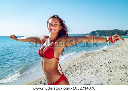 Beautiful young woman having fun on the beach. She is standing with open arms and pensive looking away with smile on her face.