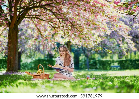 Beautiful young woman having picnic on sunny spring day in park during cherry blossom season, reading a book #591781979