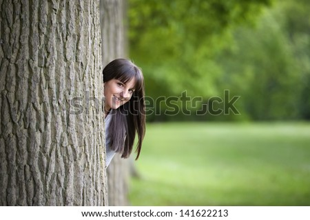 beautiful young woman hiding behind a tree