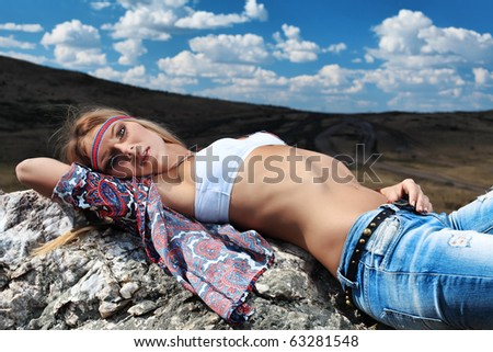 Beautiful young woman hippie posing over picturesque landscape.