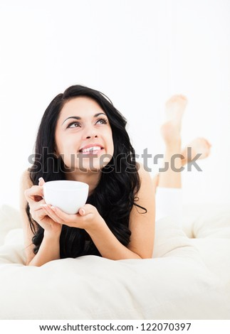 beautiful young woman hold cup of coffee lying think relaxing on the couch, sofa home indoors, happy smile day dreaming with tea mug in hands looking up away in thought