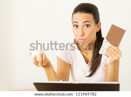 Beautiful young woman holding a Chocolate and Stress Ball in her hands in the workplace. - stock photo