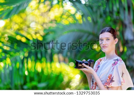 Beautiful young woman holding a digital camera in a colorful green and yellow garden backdrop