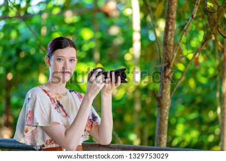 Beautiful young woman holding a digital camera read to take a photo in a colorful garden background