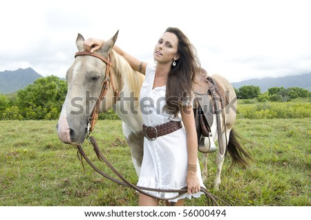 beautiful young woman holding a horse by the rains in a Kauai ranch