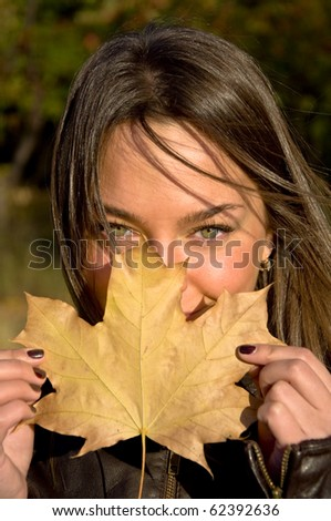 Beautiful young woman holding a maple leaf. Looks into the camera with green eyes. Autumn portrait.