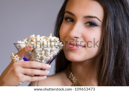 Beautiful young woman holding a martini glass filled with popcorn. - stock photo
