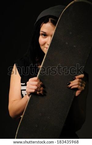 beautiful young woman holding a skateboard