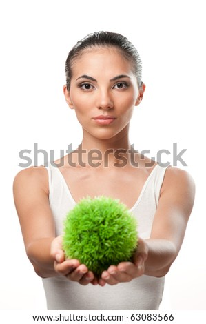 Beautiful young woman holding a sphere of green grass, symbol of care and protection of the natural environment