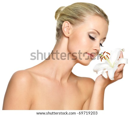 Beautiful young woman holding  a white lily at face, isolated on white