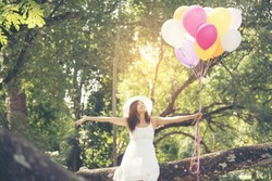 Beautiful young woman holding air balloons in garden. Relax Girl freedom life. Travel Concept.