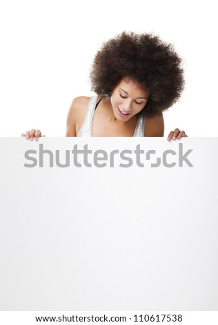 Beautiful young woman holding and looking to a white billboard with copy space, isolated on white