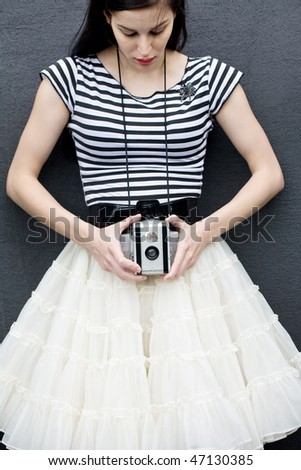 Beautiful young woman holding antique twin lens camera