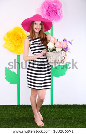 Beautiful young woman holding basket of flowers on decorative background