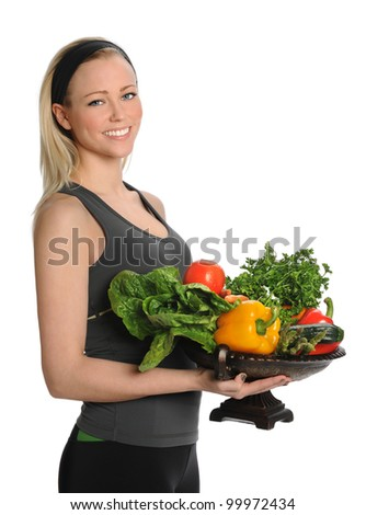 Beautiful young woman holding bowl with fruits and vegetables isolated over white background