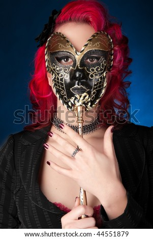 Beautiful young woman holding carnival mask