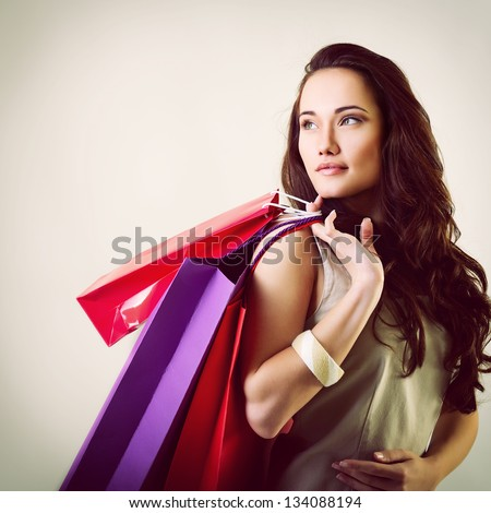 beautiful young woman holding colored shopping bags, toned